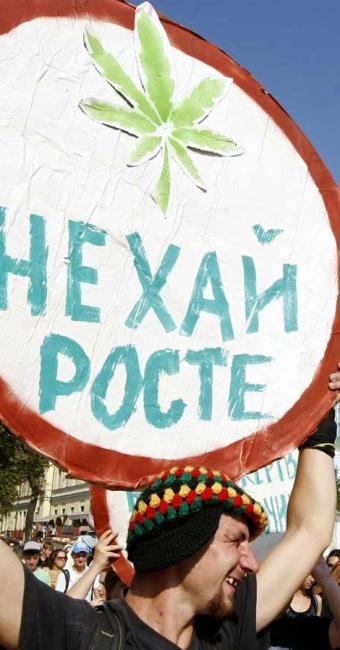 Simpatizante da legalização do maconha ergue placa em Kiev, Ucrânia, onde diz: