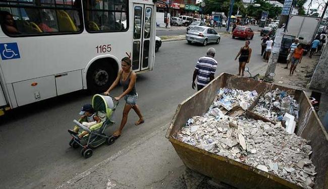 Mãe empurra carrinho de bebê na pista de veículos porque conteiner de entulho atravanca a calçada - Foto: Raul Spinassé | Agência A TARDE