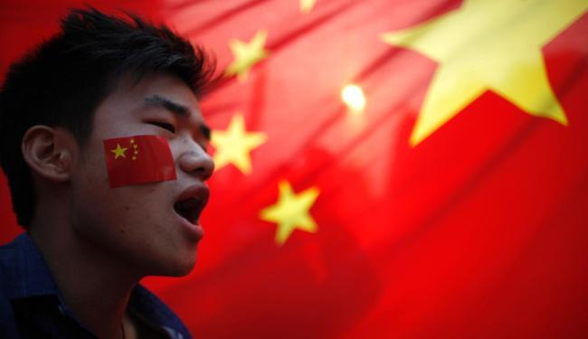 Manisfestante grita durante protesto em frente a bandeira da china em xangai - Foto: Carlos Barria | Agência Reuters