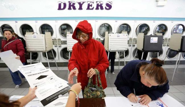 Eleitora vota em posto montado em uma lavanderia - Foto: John Gress | Ag. Reuters