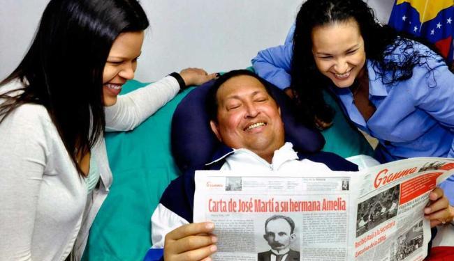 Chávez lê jornal ao lado das filhas - Foto: Agência Reuters