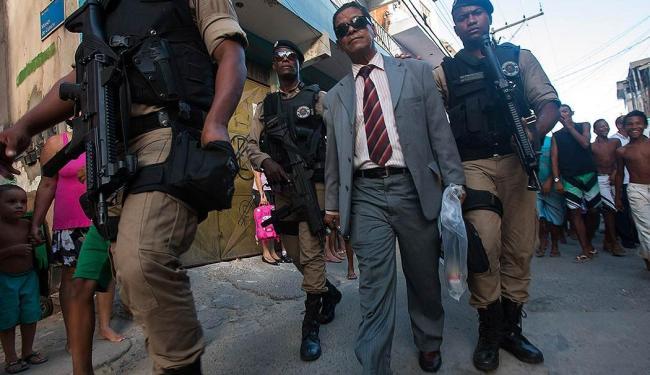 Sob protestos de vizinhos, policiais conduzem o pastor para a delegacia - Foto: Dorivan Marinho | Ag. A TARDE