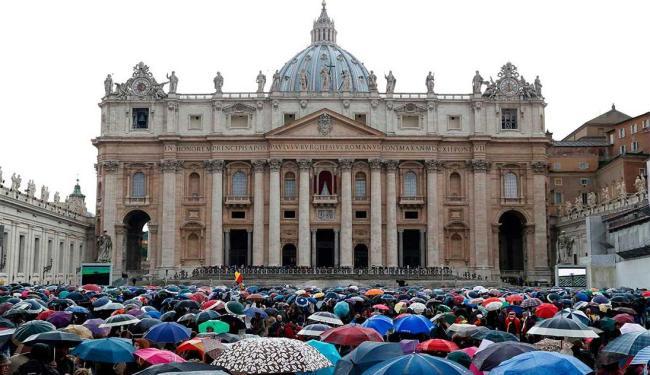 Fiéis esperam sob chuva os a fumaça das votações do conclave - Foto: Agência Reuters