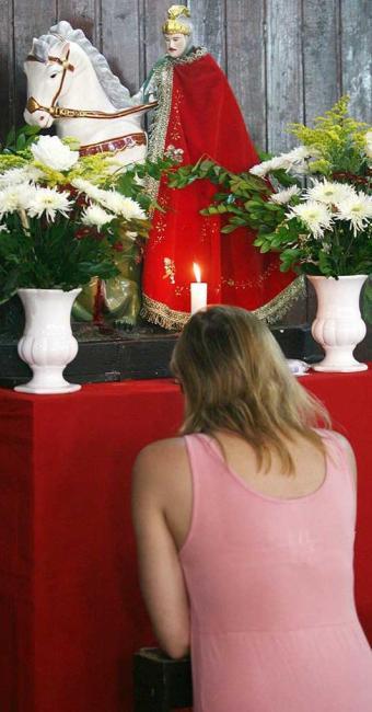 Devota ora em frente ao altar de São Jorge em Salvador - Foto: Raul Spinassé | Ag. A TARDE