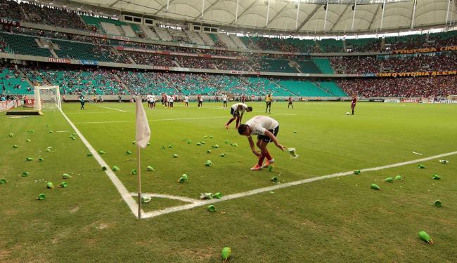 Jogadores do Bahia catam os objetos que alguns torcedores jogaram no gramado - Foto: Eduardo Martins | Ag. A TARDE