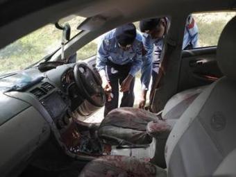 Policiais coletam evidências do carro no qual o promotor Zulfikar estava ao ser atacado - Foto: Mian Khursheed | Reuters