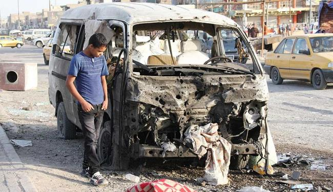 Garoto observa um dos quatro carros-bomba explodidos no Iraque nesta quinta - Foto: Agência Reuters