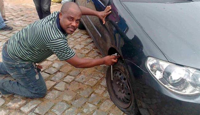 Adailton Silva precisou parar sua viagem para trocar o pneu após cair em buraco - Foto: Edilson Lima | Ag. A TARDE
