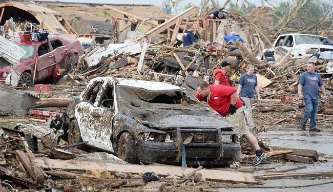Pessoas procuram por vítimas e objetos nos destroços de carros e prédios - Foto: Agência Reuters