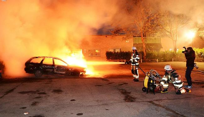 Bombeiros tentam apagar fogo de carro incendiado por manifestantes - Foto: Agência Reuters
