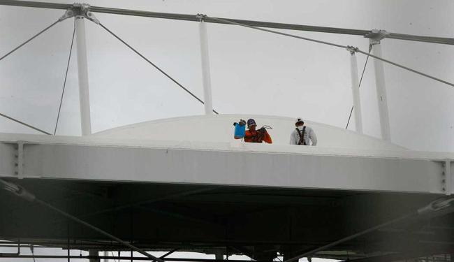 Funcionários retiram água acumulada com balde - Foto: Marco Aurélio Martins | Ag. A TARDE