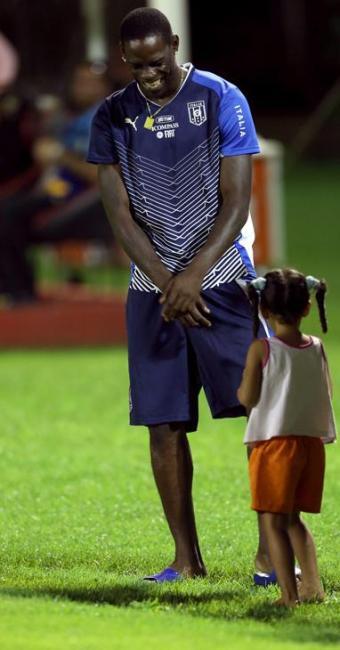 Descontraído, Balotelli brinca com uma garota baiana durante treino no Barradão nesta quinta, 20 - Foto: Antonio Lacerda / Agência EFE