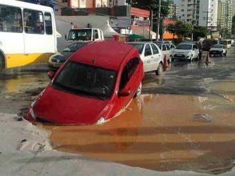 Carro ficou com a frente presa em um buraco no Imbuí - Foto: Edilson Lima | Ag. A TARDE