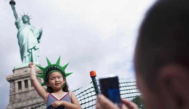 Criança posa para foto em frente à estátua - Foto: Agência Reuters