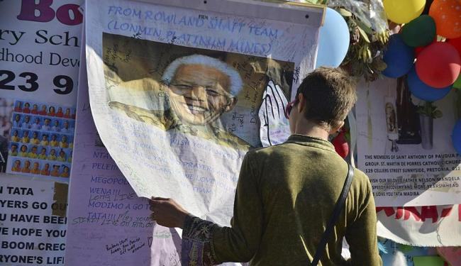 Mulher lê um dos cartazes pregados na grade do hospital onde Mandela está internado - Foto: Agência Reuters