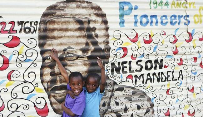 Crianças brincam em frente a mural pintado com imagem de Nelson Mandela - Foto: Agência Reuters