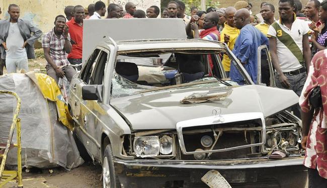 Curiosos observam um carro destruído em uma das explosões ocorridas em Kano - Foto: Agência Reuters