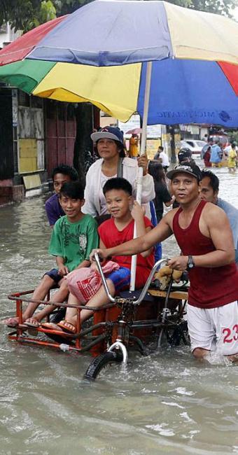Moradores de Manila buscam alternativas para sair de casa com ruas alagadas - Foto: Agência Reuters