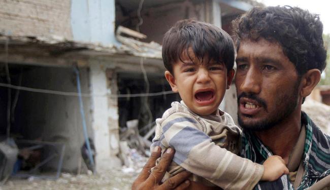 Criança afegã chora no colo de policial após atentado - Foto: Agência Reuters