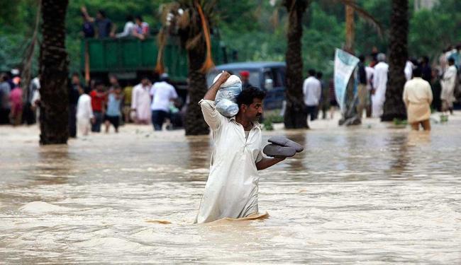 Homem carrega seus pertences no ombro enquanto passa por uma área alagada - Foto: Agência Reuters