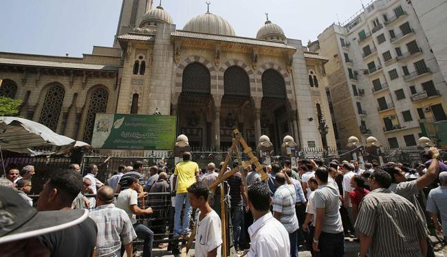 Manifestantes anti-Mursi e policiais de choque se reúnem em frente a mesquita no Cairo - Foto: Agência Reuters