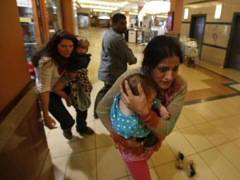 Mulheres com crianças tentam se proteger durante ataque - Foto: Goran Tomasevic | Reuters