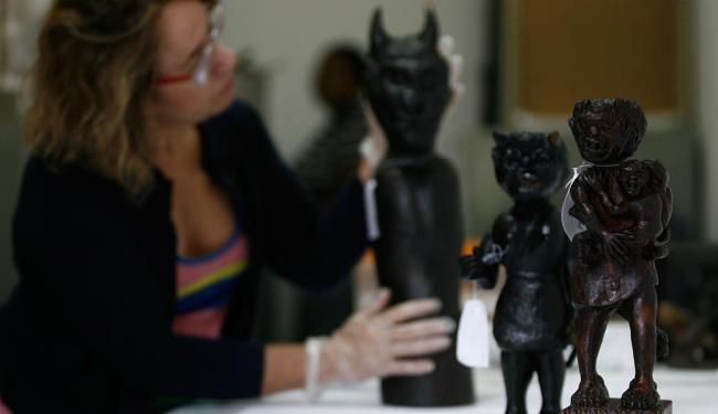 A diretora do Mafro, Graça Azevedo, exibe uma das estatuetas que integram a coleção - Foto: Raul Spinassé | Ag. A TARDE