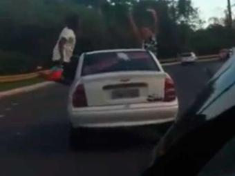 Casal brinca e dança pendurado em janela de carro em movimento - Foto: Reprodução | Youtube