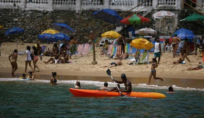 Homem rema em caiaque bem próximo a banhistas na praia do Porto da Barra - Foto: Raul Spinassé | Ag. A TARDE