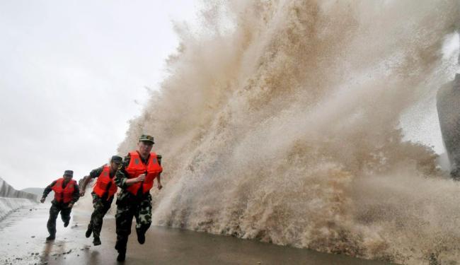 Policiais correm de onda gigante em dique da China - Foto: Agência Reuters