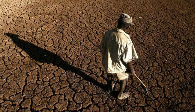 Trabalhador rural procura por vestígios de água em açude - Foto: Raul Spinassé | Ag. A TARDE