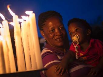 Mulher segura uma criança e reza por Mandela na África do Sul - Foto: REUTERS