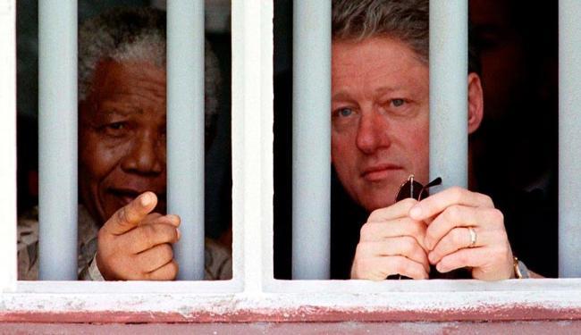 Mandela e Bill Clinton entre as grades da cela da prisão que o sul-africano passou 17 anos - Foto: Rick Wilking | Agência Reuters