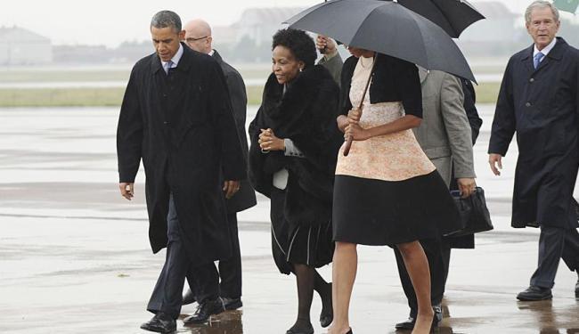 Sob chuva, Obama chega acompanhado do ex-presidente George Bush - Foto: Agência Reuters