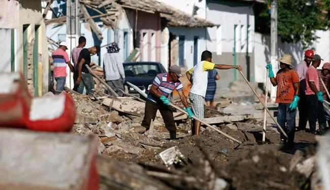 Trabalho pesado para desobstruir a rua do Canal - Foto: Raul Spinass | Ag. A TARDE