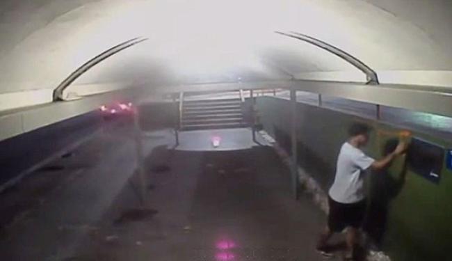 Homem parou o carro e desceu para pichar a passarela - Foto: Reprodução