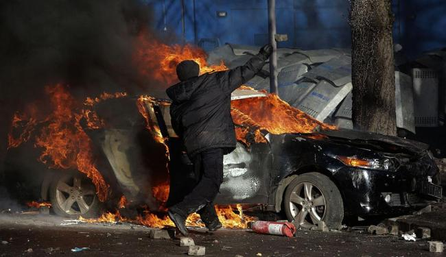Manifestantes jogam pedras contra a polícia durante confronto em Kiev - Foto: Konstantin Chernichkin   Reuters