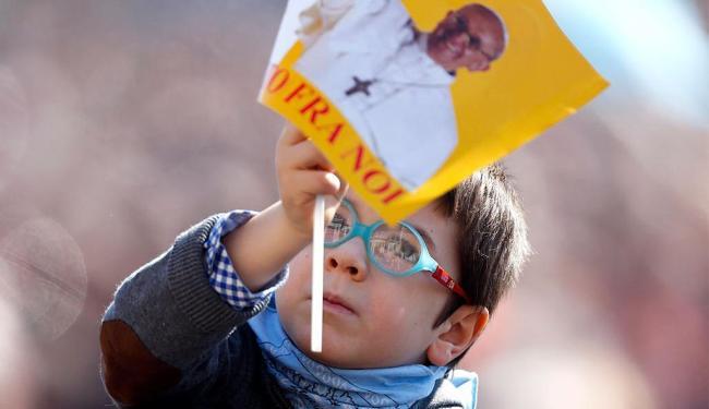 Criança sacode bandeira com a imagem do papa durante a missa de Angelus, na praça São Pedro - Foto: Agência Reuters