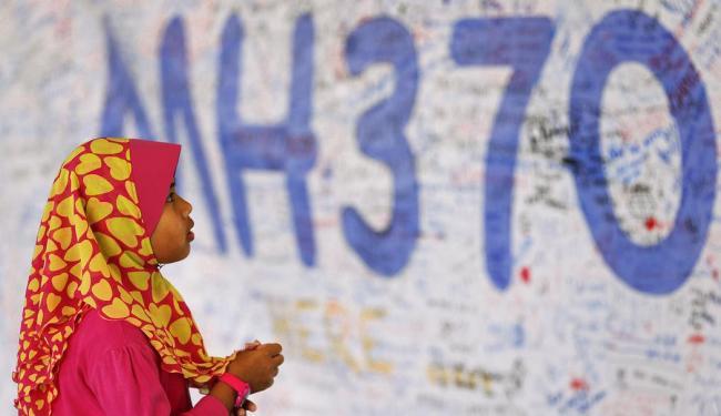 Menina olha para painel com mensagens sobre o voo MH370 - Foto: Damir Sagolj | Reuters