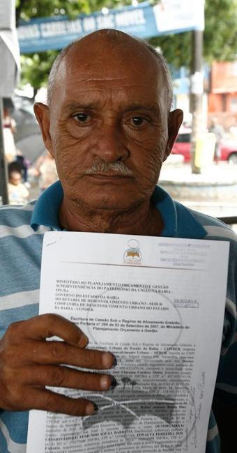 O aposentado Edmundo Barreto, de 72 anos, comemora o recebimento da escritura - Foto: Luciano da Matta   Ag. A TARDE