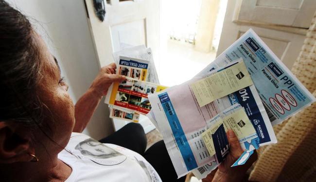 Vilma Pereira mostra todos os comprovantes de IPTU quitados nos últimos anos - Foto: Mila Cordeiro | Ag. A TARDE
