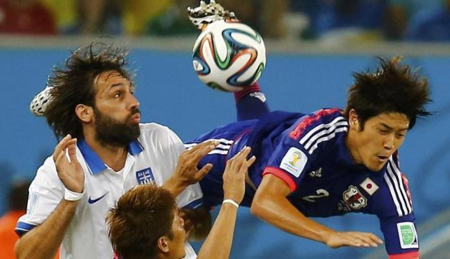 Na disputa de bola, o atacante grego Samaras (E) tenta se livrar da rápida marcação dos japoneses - Foto: Kai Pfaffenbach | Ag. Reuters