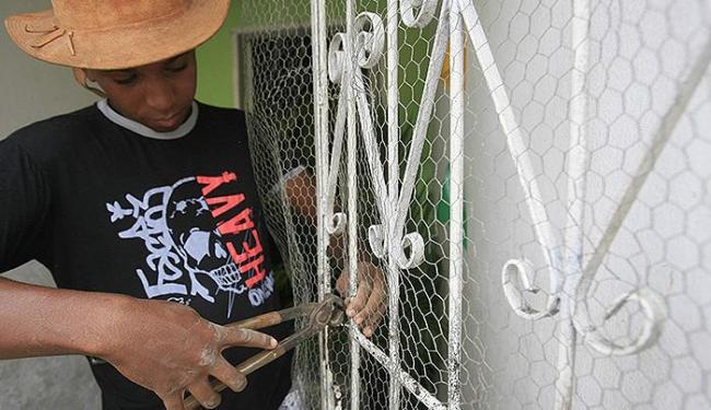 O jovem Wellington Santos instala uma tela na porta para evitar que espadas entrem na casa - Foto: Joá Souza l Ag. A TARDE