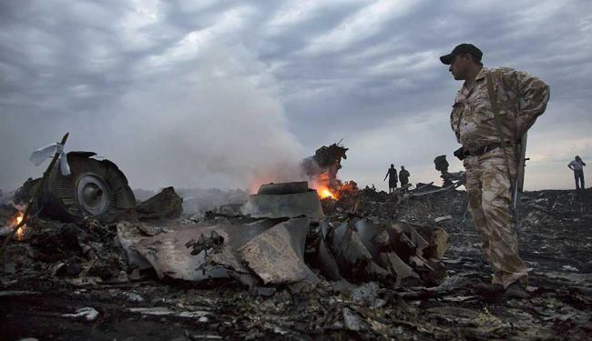 Militar separatista observa os destroços do voo MH17 da Malaysia Airlines - Foto: Dmitry Lovetsky | AP
