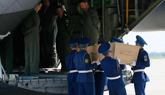 Guardas colocam caixões com corpos em avião para transporte até a Holanda - Foto: Agência Reuters