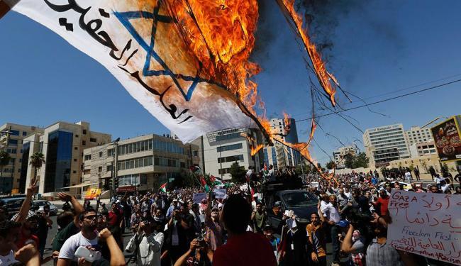 Manifestantes jordanianos queimar bandeira representando Israel - Foto: Agência Reuters