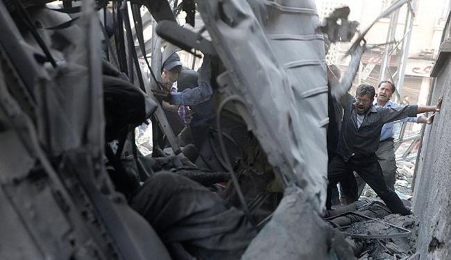 Homens procuram sobreviventes em destroços de ataque - Foto: Agência Reuters