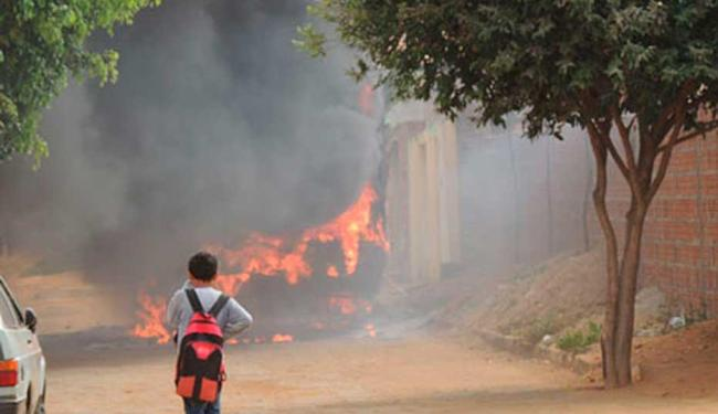 Criança observa ônibus escolar destruído, e população teme que ameaças a escola sejam concretizadas - Foto: Lay Amorim | Brumado Notícias
