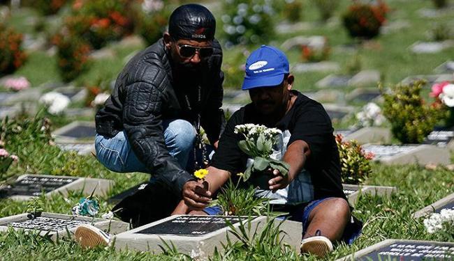 Joenilson da Silva Santos e Roque Bispo enfeitaram o túmulo do 'mestre' com flores - Foto: Raul Spinassé   Ag. A TARDE