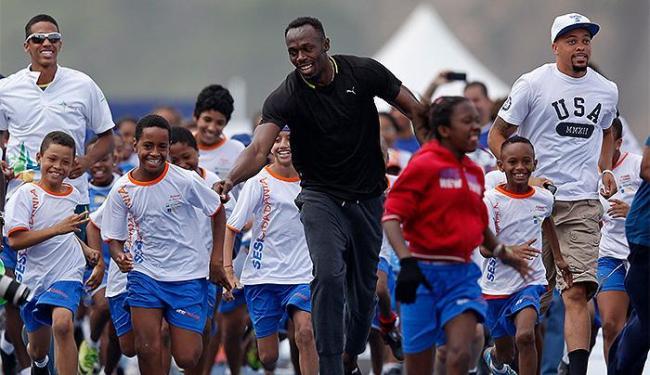 Na véspera do desafio, velocista jamaicano correu com crianças de comunidades cariocas - Foto: Pilar Olivares l Reuters